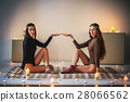 Two young women relax on plaid and holding candles in hands 28066562