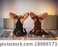 Two young women doing yoga asana lotus in shoulder stand pose on 28066573