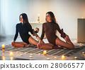 Two young women doing yoga asana Eka Pada Rajakapotasana on plai 28066577