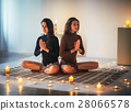 Two young women  meditating in lotus pose with hands in namaste 28066578