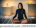 Young beautiful woman meditating on lotus pose in cozy room with 28066968