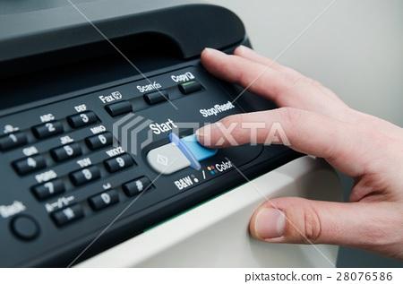Finger on start button of laser printer 28076586