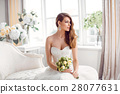 Bride in beautiful dress sitting resting on sofa 28077631