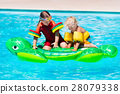Kids in swimming pool with inflatable toy 28079338