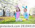 Easter egg hunt. Kids with bunny ears in garden. 28104019