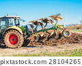 Tractor plowing a field 28104265