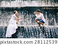 Family honeymoon holiday. Couple in waterfall pool 28112539