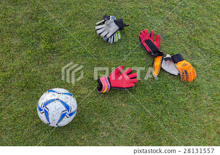 soccer gloves and ball on grassy field 28131557