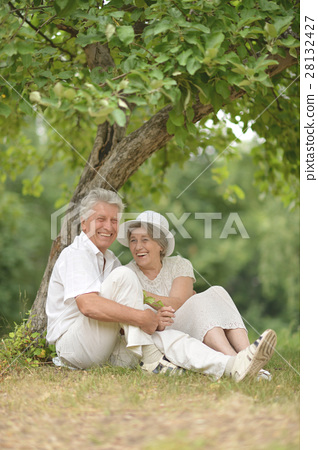 Senior couple sit on a ground in summer forest 28132427