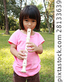 Young girl playing flute in park 28133639