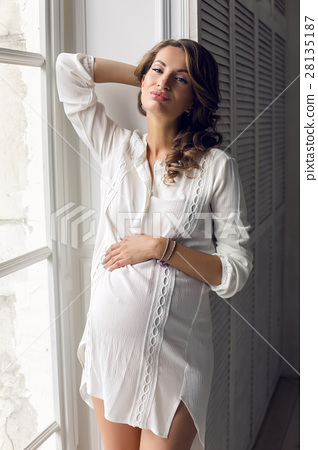 young pregnant woman in white dress in the studio 28135187