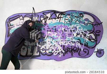 Young girl tagging wall with graffiti 28164310