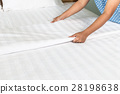 Hand set up white bed sheet in hotel room 28198638