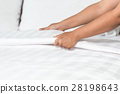 Hand set up white bed sheet in hotel room 28198643