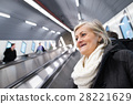 Senior woman standing at the escalator in Vienna 28221629
