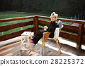 Senior woman on wooden terrace, resting with feet 28225372