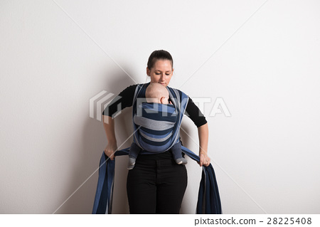 Beautiful young mother wrapping her son into sling 28225408