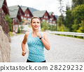 Young fitness woman jogging on street of town 28229232