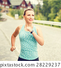 Young fitness woman jogging on street of town 28229237