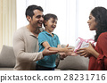 Father holding son while mother snatching gift  28231716