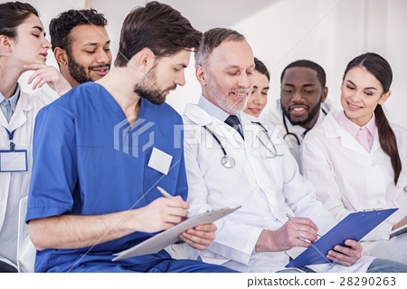 Cheerful doctors watching at tablet of colleague 28290263