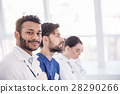 Smiling doctor with colleagues situating in 28290266