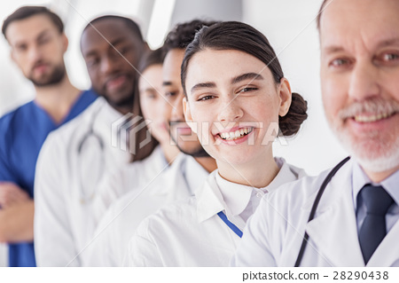 Smiling doctor situating near her colleagues in 28290438