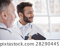 Smiling physician telling with doctor in hospital 28290445