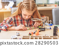 Serious concentrated little girl in workshop 28290503