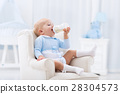 Baby boy with bottle drinking milk or formula 28304573