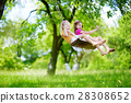 Two cute little sisters having fun on a swing together in beautiful summer garden 28308652