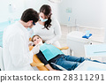Dentist trearing child in his surgery 28311291