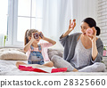 Mother and her daughter eating donuts 28325660