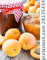 ripe apricot fruits and jar of jam on table 28335434