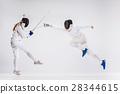 The men and woman wearing fencing suit practicing 28344615