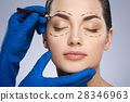Plastic surgeon drawing dashed lines above eyebrow 28346963