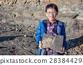 Young asian boy holding stone with fossil inside 28384429