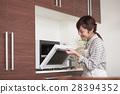 주방에 서서 전자 레인지를 사용하는 여성 28394352