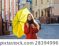 young woman with a yellow umbrella walking in the 28394996