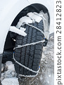 Snow chain puts on a wheel of a car 28412823