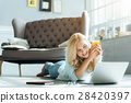 Happy woman drinking juice in living room 28420397