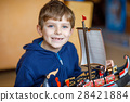 Little blond preschool kid boy playing with toy 28421884