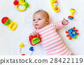 Cute baby girl playing with colorful rattle toys 28422119