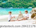 Two kid boys building sand castle on tropical 28422176