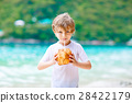 Little kid boy drinking coconut juice on tropical 28422179