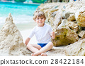 Little kid boy building sand castle on tropical 28422184