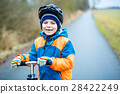 Cute preschool kid boy riding on scooter in park 28422249