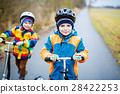 Two little kid boys, best friends riding on 28422253