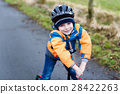 Cute preschool kid boy riding on scooter in park 28422263