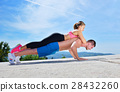 Active young man and woman exercising doing push 28432260
